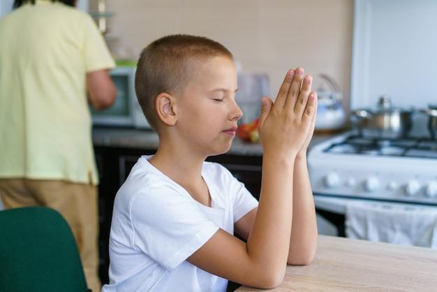백인 소년은 집에서 식사하기 전에 집에서 기도하고 집에서 온라인 교회 예배를 위해 기도합니다.
