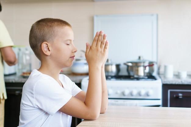 白人の少年は、食事をする前に家でテーブルで祈って家にいて、神のオンライン教会の奉仕に祈っています...