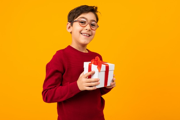 Caucasian boy in a red jumper with a gift box on yellow with copy space