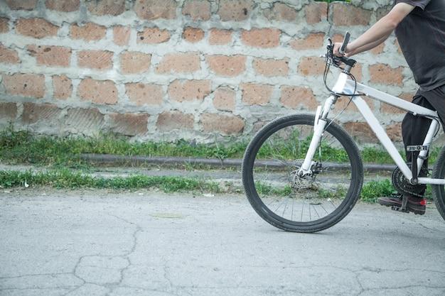 アスファルトで自転車に乗る白人の少年。