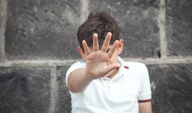 Caucasian boy showing stop gesture.