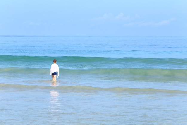 Caucasian boy white shirt having fun with big white wave over green ocean blue sky