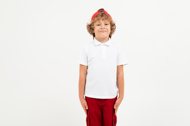 Caucasian boy in white t-shirt, red cap, red shorts smiles isolated on white background