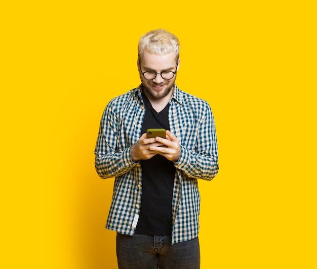 ブロンドの髪とひげを持つ白人の少年は、空きスペースのある黄色の背景でポーズをとっている間誰かとチャット