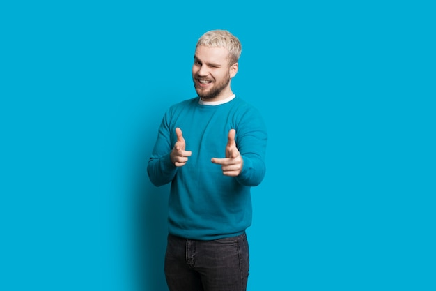 Caucasian boy with blonde hair is pointing to camera while smiling and posing on a blue wall
