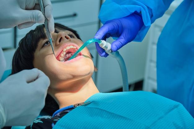 치과의사 사무실에서 갈색 머리를 한 백인 소년이 치과 인상을 위해 알지네이트 몰드를 넣고 있다