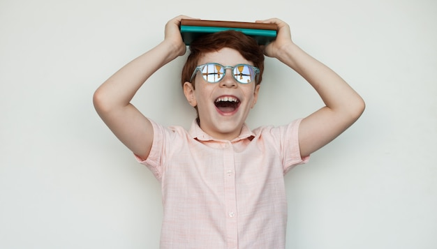 Caucasian boy with ginger hair and glasses is holding some book on his head and smile on a white  wall