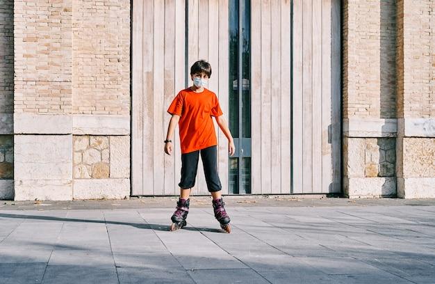 公園でローラースケートで遊んでいるマスクを持つ白人の少年。