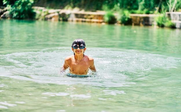 여름에 강 안의 카메라를 보고 물 안경을 쓴 백인 소년.