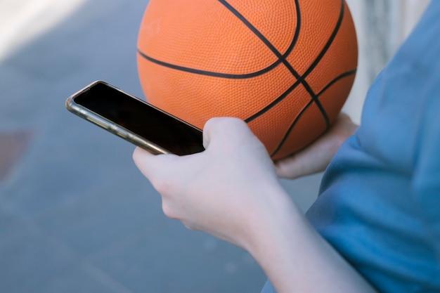 バランスボールと携帯電話で白人の男の子の手