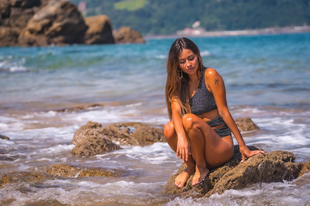 Caucasian brunette black swimsuit with sparkles enjoying the summer at sea. refreshing on the seashore by the waves