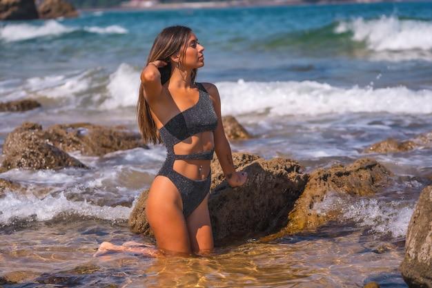 Кавказская брюнетка в черном купальнике с блестками наслаждается летом на море. охлаждение в морской воде на коленях