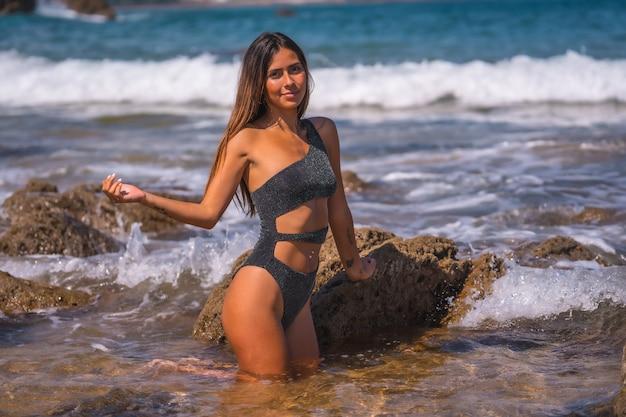 Кавказская брюнетка в черном купальнике с блестками наслаждается летом на море. освежение в морской воде