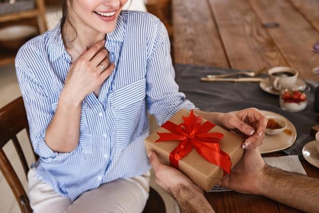 白人ブルネットカップルの男性と女性がプレゼントボックスとテーブルに座っている間アパートで朝食をとる