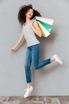 Caucasian brunette female in casual posing on camera with a lot of packages in hand being satisfied after shopping over grey wall