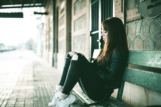 Caucasian brunette female sitting on the bench behind a building and waiting for the train