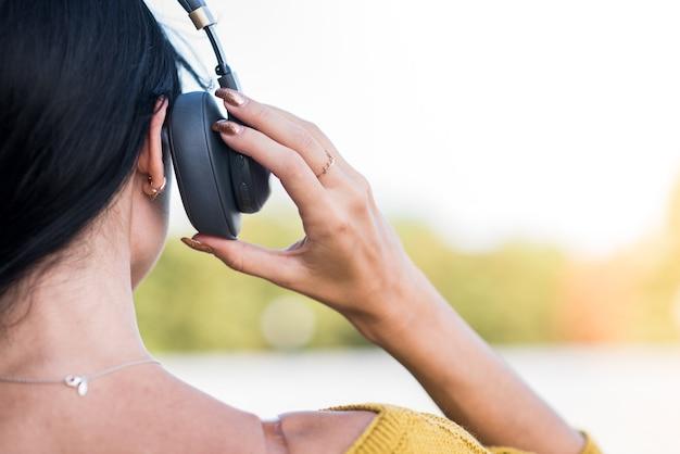 ヘッドフォンで白人ブルネットの女の子。背面図。