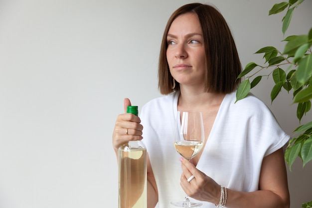 Caucasian brunette girl sommelier holding glass of white wine