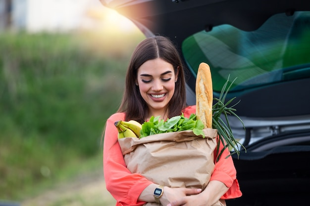 Caucasian brunette going holding paper bags with food products. young woman putting package with groceries and vegetables into car trunk.