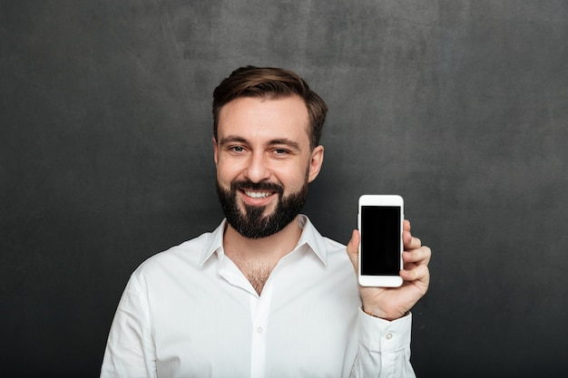 Caucasian brunette man showing smartphone on camera demonstrating or advertising gadget over graphite copy space