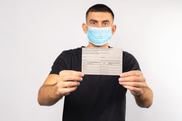 의료 마스크를 쓰고 백인 갈색 머리 남자 보유 코로나 바이러스 예방 접종 카드 흰색 격리 된 배경