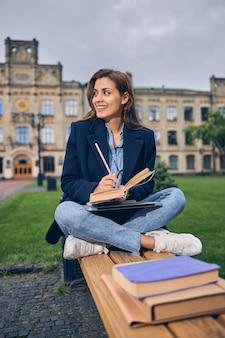 외부 벤치에서 공부하는 동안 무릎에 그녀의 노트북과 함께 앉아 백인 갈색 머리 학생