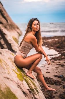 海辺で茶色の水着と白人ブルネット