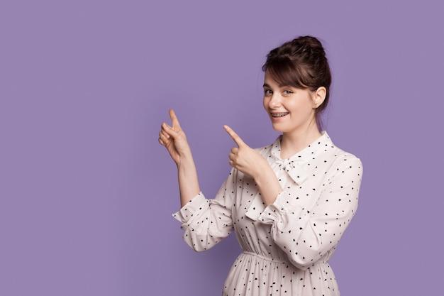 드레스와 치과기구를 입고 백인 갈색 머리 여자는 보라색 스튜디오 벽에 여유 공간을 가리키는