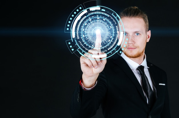 Caucasian business man in black suit hand touching virtual screen graphic diagram on dark background