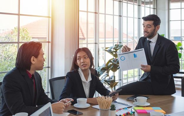백인 비즈니스 여자와 아시아 공동 작업자 모양과 회의실에서 남자 동료 설명 차트를 들어요.