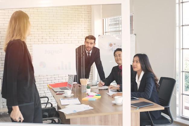 Кавказская бизнес-леди, давая диаграмму представления диаграммы в бизнес-семинаре с многоэтническим коллегой на рабочем месте.