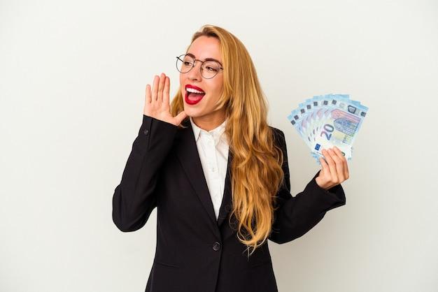 開いた口の近くで叫び、手のひらを保持している白い背景で隔離の請求書を保持している白人のビジネス女性。