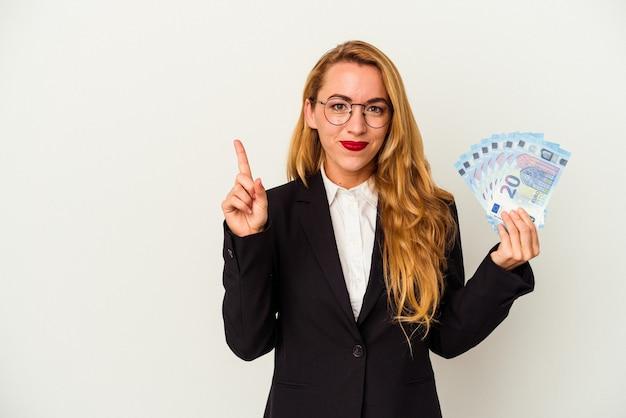指でナンバーワンを示す白い背景で隔離の請求書を保持している白人のビジネス女性。