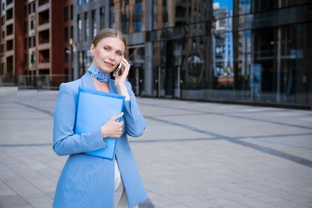 Кавказская деловая женщина в синем пиджаке и платье разговаривает по телефону с папкой с бумагами в руке