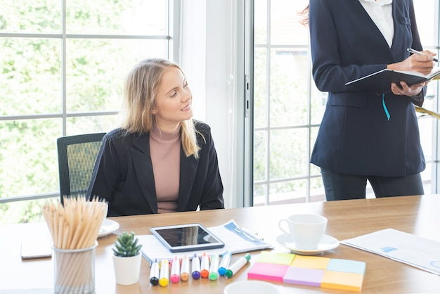 Caucasian business woman sit and look in meeting conference room with multi ethnic co-worker.