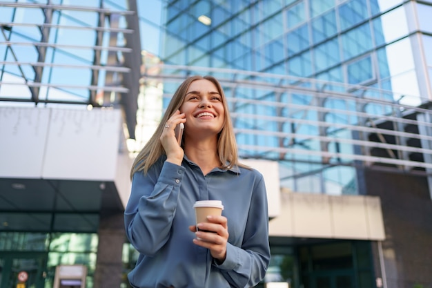 Caucasian business woman speaking by phone holding coffee to go. a successful european woman, talking on the phone, standing on modern office building