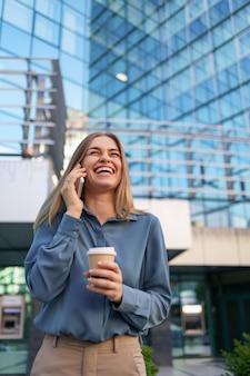 行くコーヒーを保持している電話で話す白人のビジネス女性。電話で話して、近代的なオフィスビルの上に立って成功したヨーロッパの女性