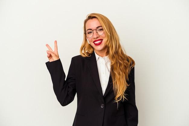 指で平和のシンボルを示す、楽しくてのんきな白い背景に分離されたワイヤレスヘッドフォンを身に着けている白人のビジネス女性。