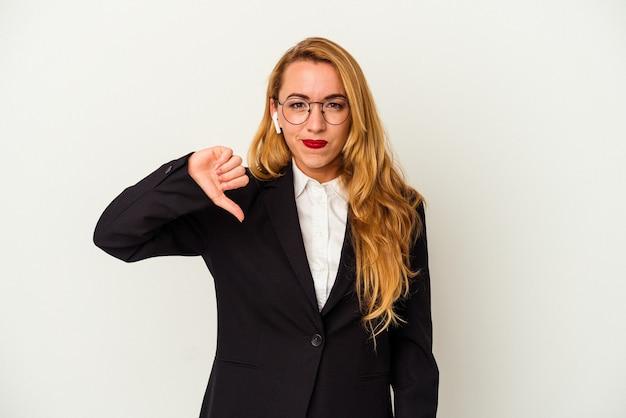 Кавказская деловая женщина в беспроводных наушниках, изолированных на белом фоне, показывает жест неприязни, пальцы вниз. концепция несогласия.