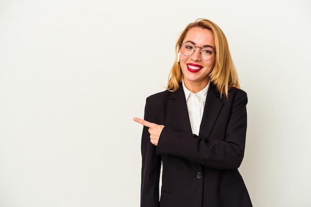 白い背景に分離されたワイヤレスヘッドフォンを身に着けている白人のビジネス女性は、笑顔で脇を指して、空白のスペースで何かを示しています。