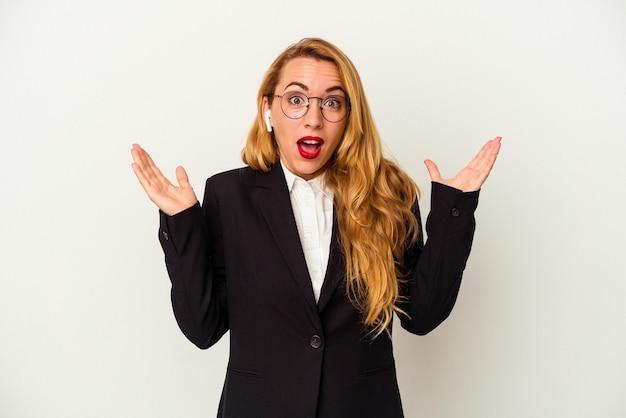 白い背景で隔離のワイヤレスヘッドフォンを身に着けている白人のビジネス女性は驚いてショックを受けました。