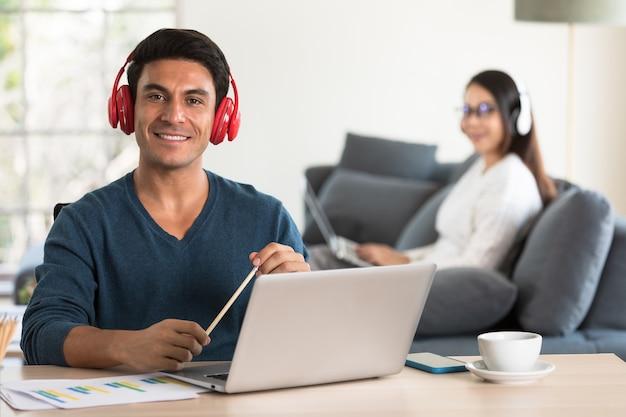 백인 사업가와 아시아 여성 사업가가 캐주얼한 드레스를 입고 거실에 함께 앉아 헤드폰을 끼고 흰색 노트북 컴퓨터 작업을 하고 있습니다. 집에서 현대적인 작업을 위한 아이디어.