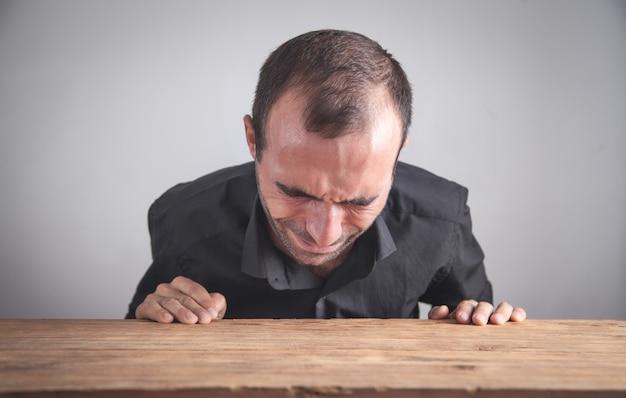Кавказский бизнесмен плачет в офисе.