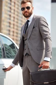 Caucasian businessman in formalwear opening the door of his representative car