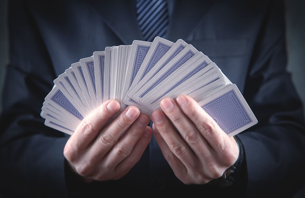 Caucasian businessman holding playing cards.
