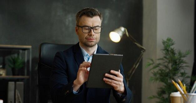 手で保持し、タブレットデバイスを使用してメガネの白人実業家。男性のテキストメッセージと画面上で入力してキャビネットで考えています。