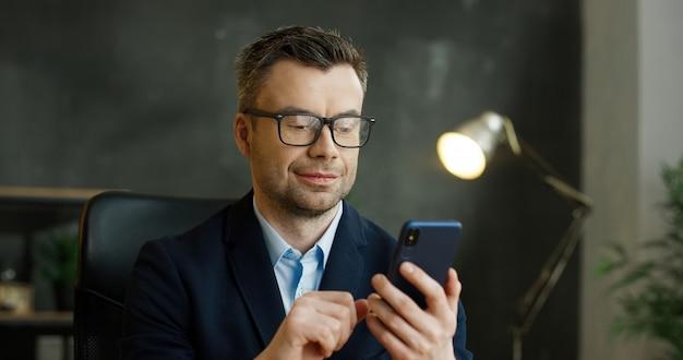 スマートフォンを手で保持しているメガネの白人実業家。男性のテキストメッセージとキャビネットに携帯電話で入力します。