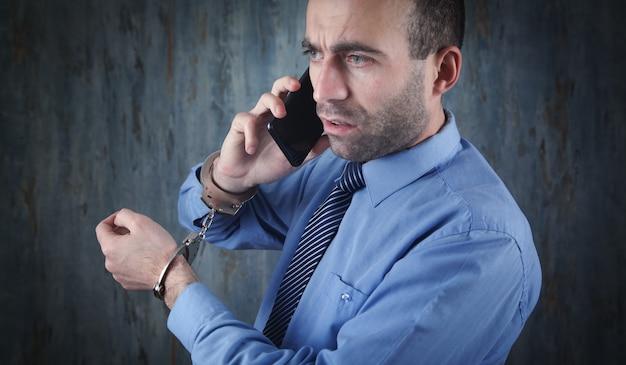 スマートフォンで話している手錠をかけた白人ビジネスマン。腐敗