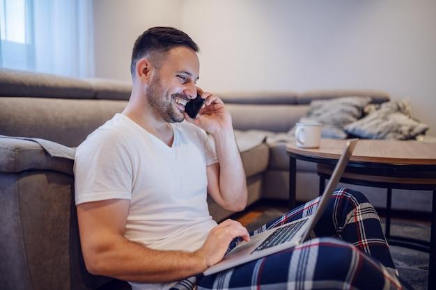 잠 옷에서 백인 사업가 거실 바닥에 앉아 노트북을 사용 하 고 아침에 스마트 폰 이야기.