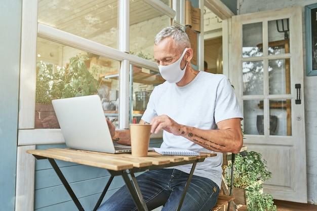 Кавказский бизнесмен в защитной маске работает на ноутбуке